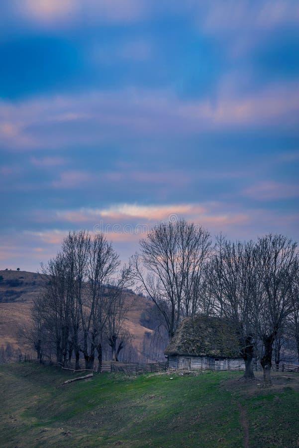 树包围的老土气美丽如画的谷仓房子在小山顶部反对早晨射击的多云天空在春天期间 免版税库存图片