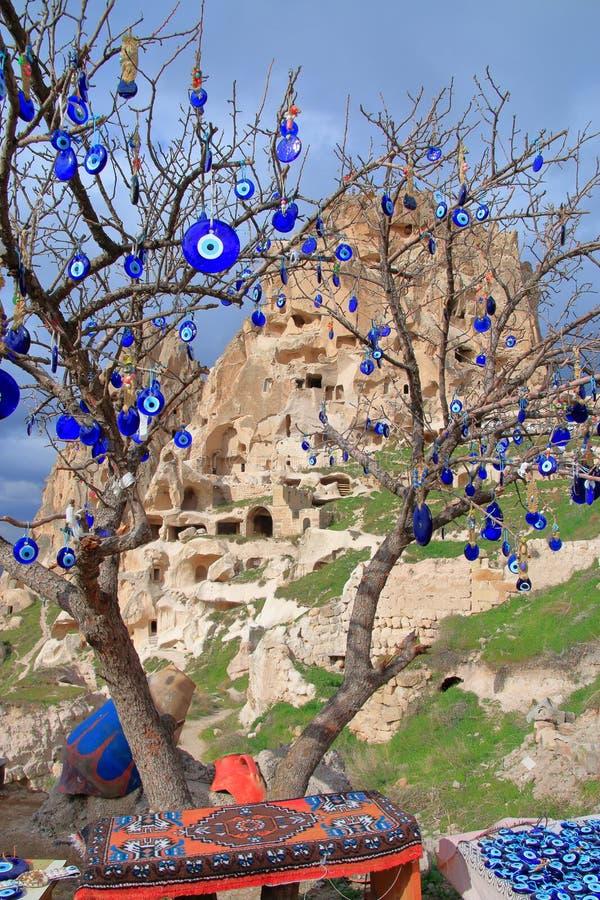 树垂悬与护身符以眼睛的形式以洞解决Uchisar为背景 免版税库存图片