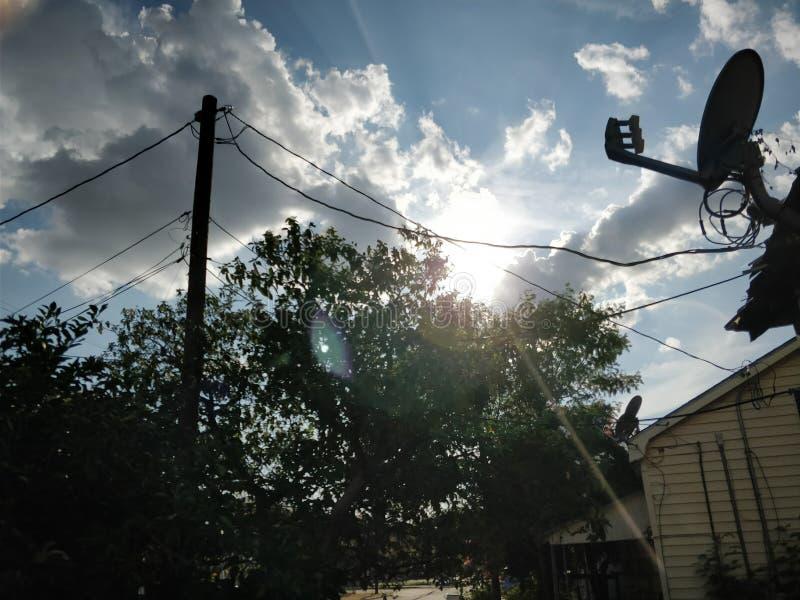 树晴朗,看法和绿色叶子 一束云彩和光在房子顶部 库存图片
