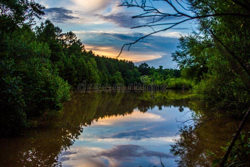 树木繁茂的火热的Clouds湖日落反射 免版税库存图片