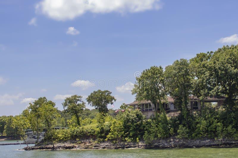 树的议院在有旗子的湖旁边和从甲板和船坞的旗布飞行有在距离-选择聚焦的小船的 库存照片