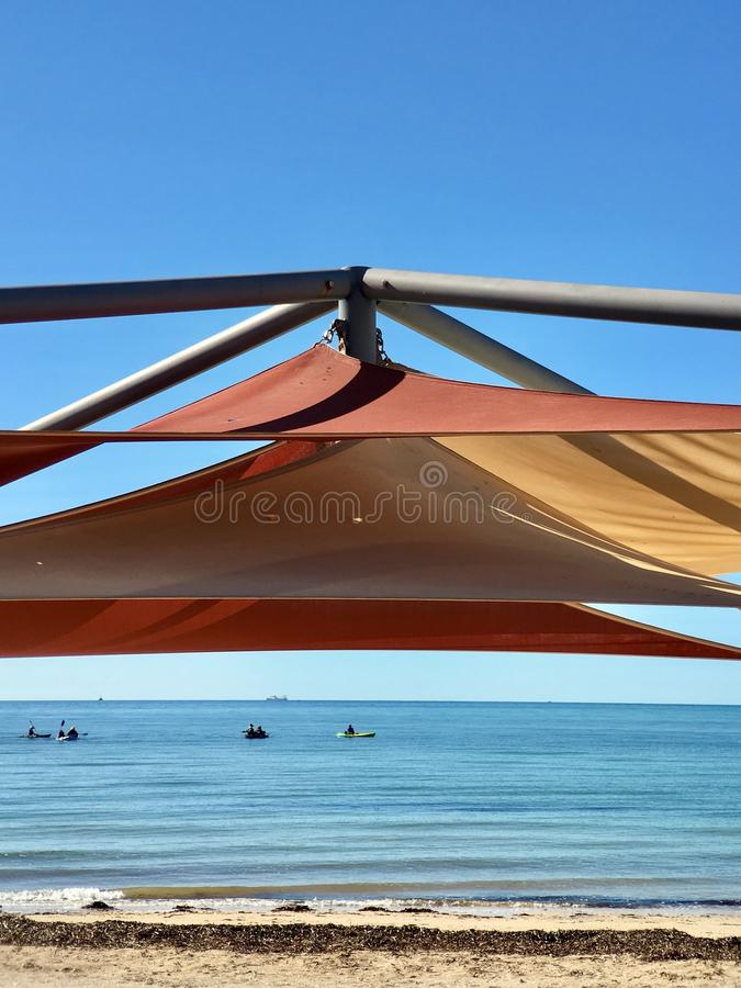 树荫在热带海滩的布料机盖 库存照片