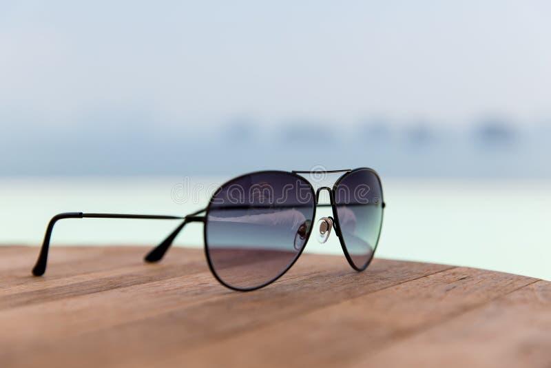 树荫或太阳镜在桌上在海滩 免版税图库摄影