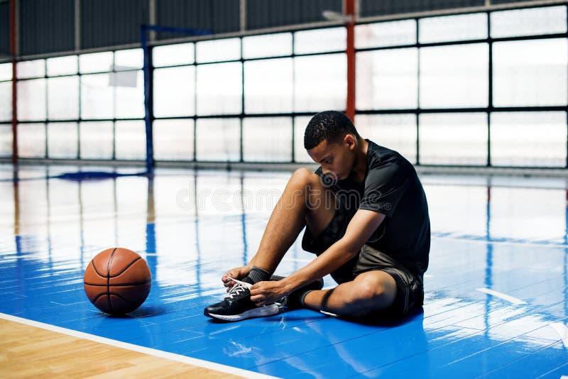 栓他的在篮球场的非裔美国人的十几岁的男孩鞋带 免版税库存图片