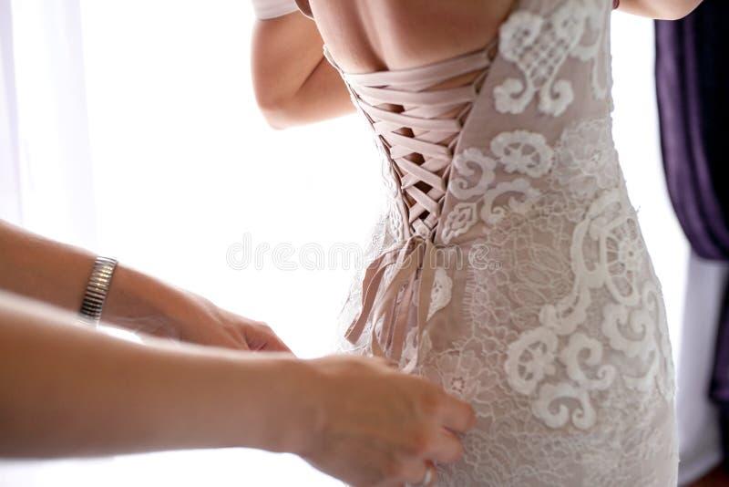 栓在婚礼礼服的女傧相弓 新娘` s准备 库存图片