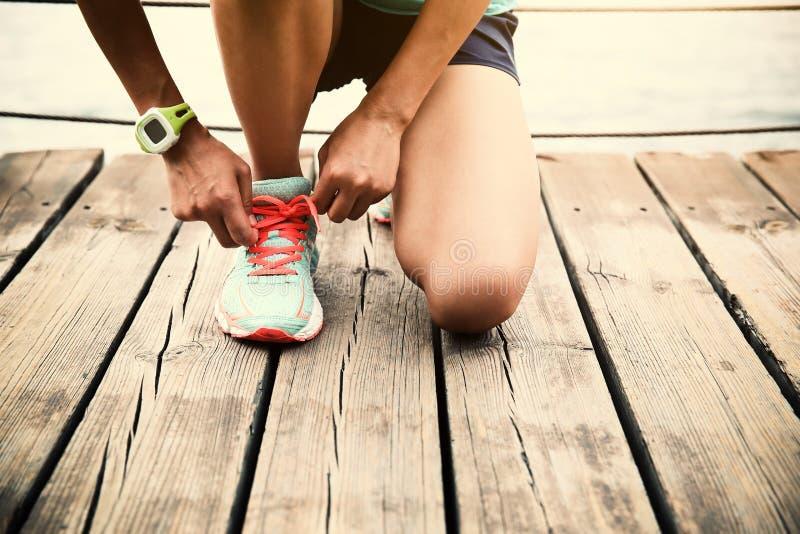 栓在木木板走道海边的妇女赛跑者鞋带 库存图片