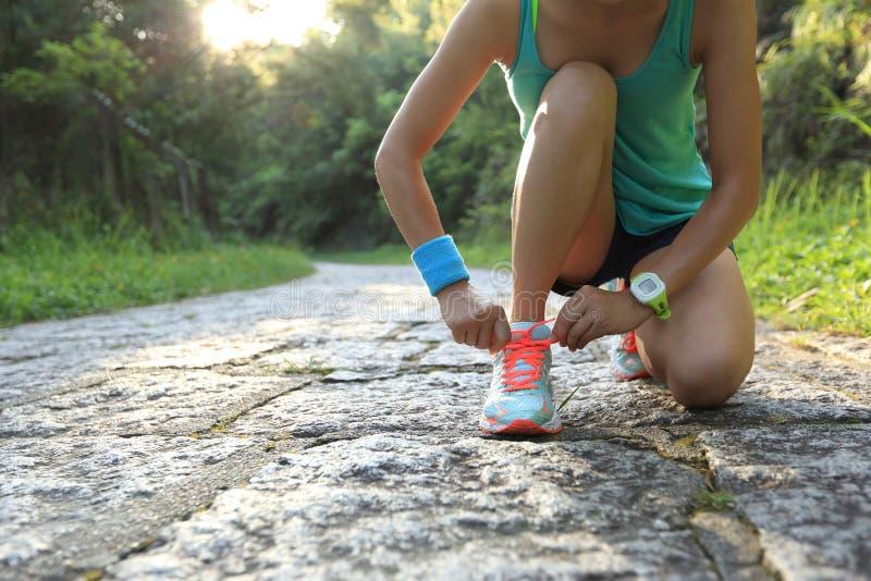 栓在石足迹的妇女赛跑者鞋带 免版税库存照片
