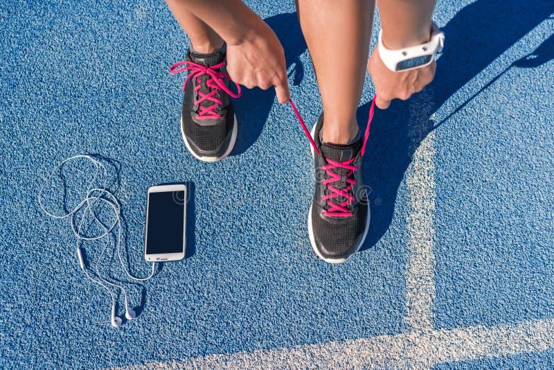 栓在种族奔跑轨道的赛跑者跑鞋鞋带 库存照片