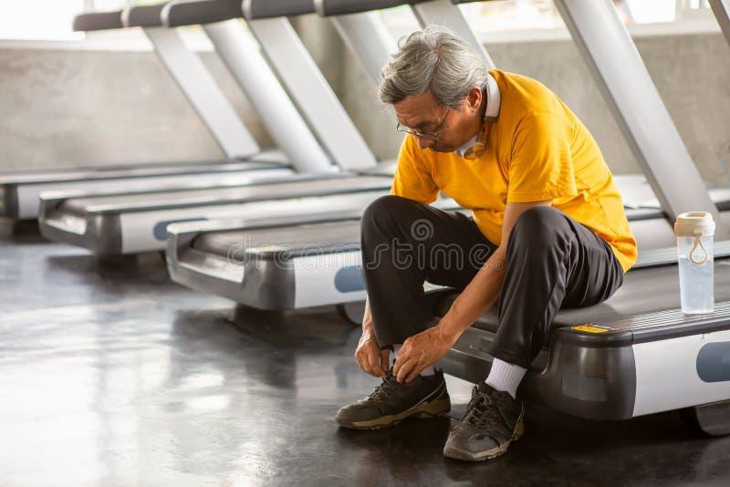栓在踏车的资深亚裔体育人鞋带在健身健身房准备好走与耳机和水瓶 更老的男性 免版税图库摄影
