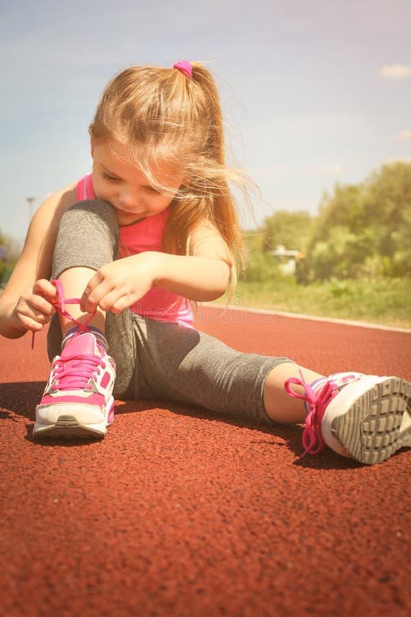 栓在运动鞋的小女孩鞋带 库存照片