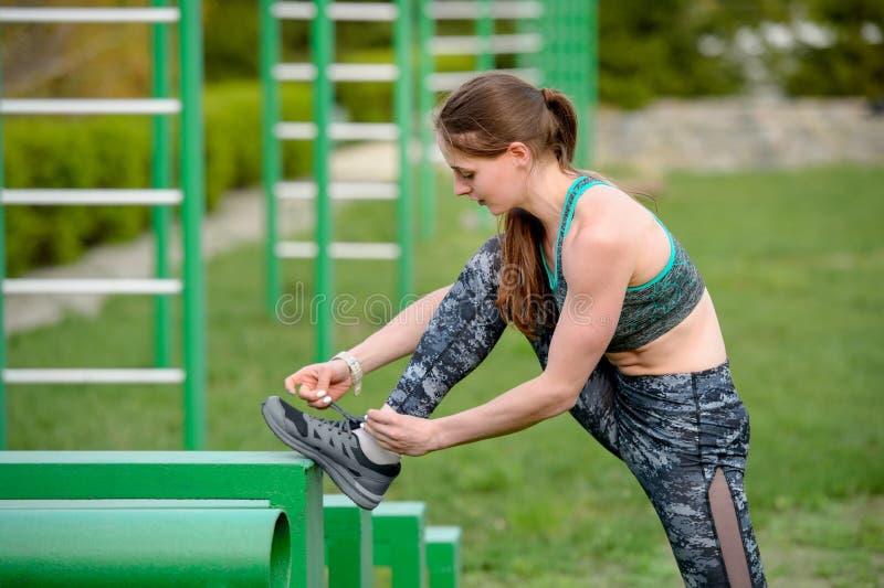 栓在运动鞋运动的妇女的运动员鞋带栓鞋带在跑前户外在晴朗的早晨 库存照片