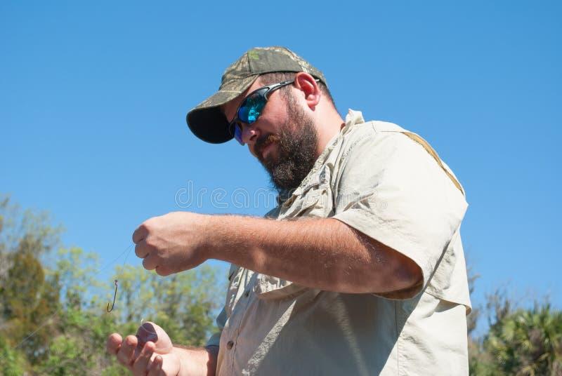 栓在钓丝上的渔夫一个勾子 免版税库存图片
