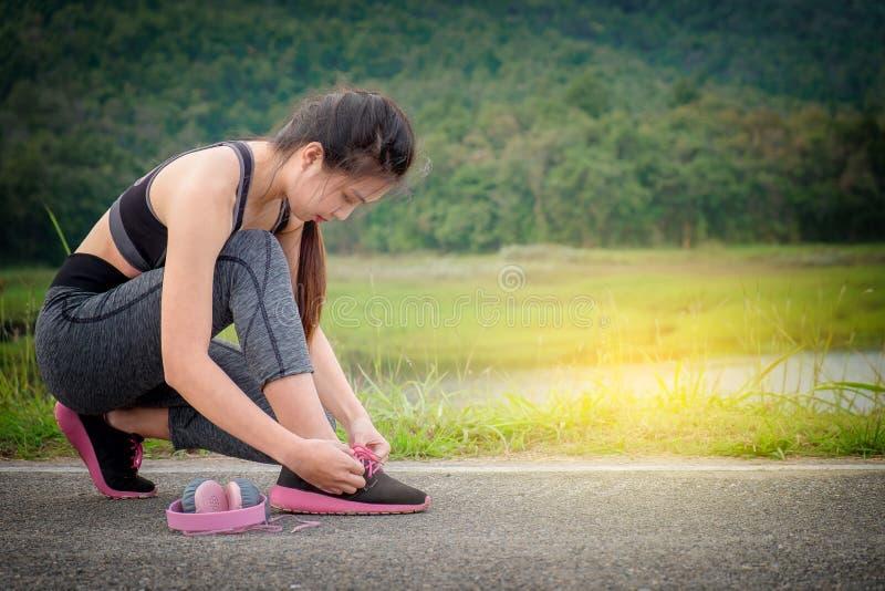 栓她的在行使的少妇席子的体育鞋子 概念  免版税库存图片