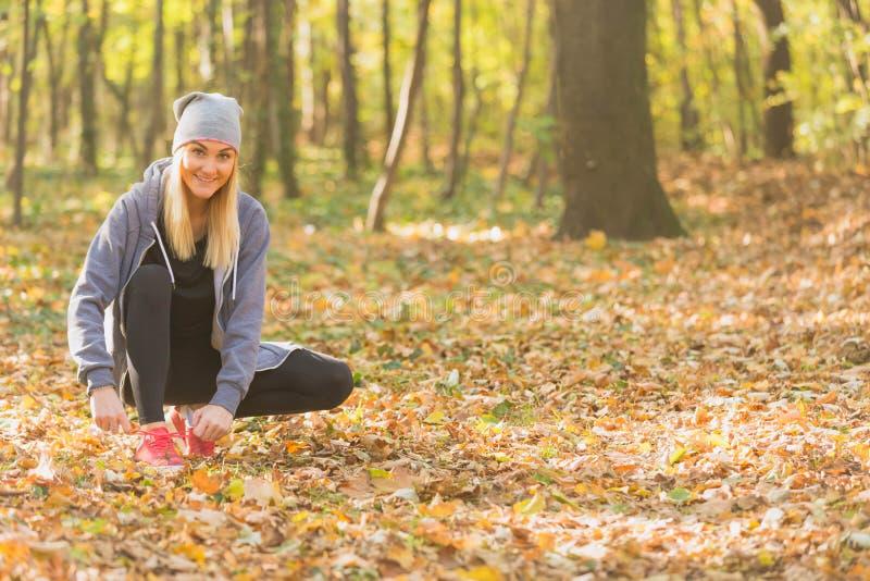 栓她的鞋子的年轻逗人喜爱的妇女在跑步前 图库摄影