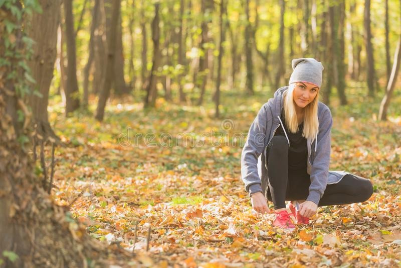 栓她的鞋带的少妇在奔跑前 健康生活方式 免版税库存图片