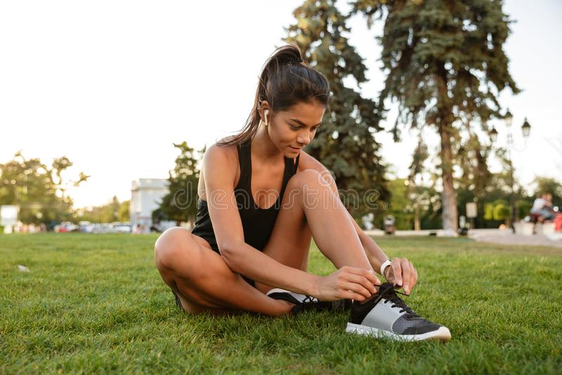 栓她的鞋带的年轻健身女孩画象  免版税库存照片