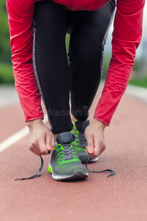 栓她的鞋带的赛跑者女孩,当跑步时 免版税库存照片
