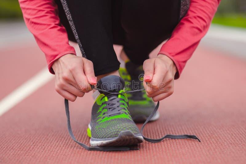 栓她的鞋带的赛跑者女孩,当跑步时 图库摄影