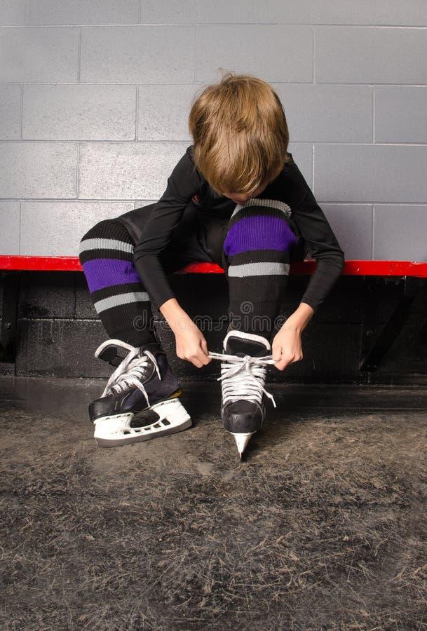 栓曲棍球冰鞋的男孩在化装室 免版税图库摄影