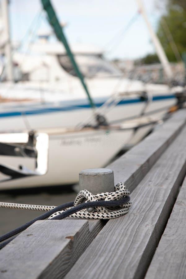 栓的小船柱子在一个木码头 有两条绳索的系船柱在码头渔船 在背景中被弄脏的小船和 库存照片