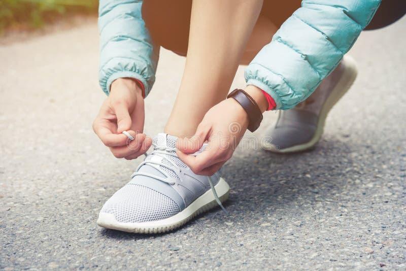 栓跑步的女孩赛跑者她的鞋子鞋带在路在公园 跑鞋,鞋带 锻炼概念 体育运动 库存图片