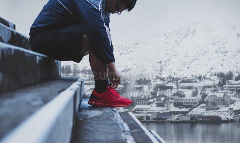 栓跑鞋的一个人,为跑做准备在冬天 健康生活方式 免版税库存照片