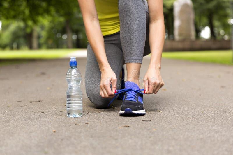 栓跑鞋的鞋带少妇在训练前 概念健康生活方式 库存图片
