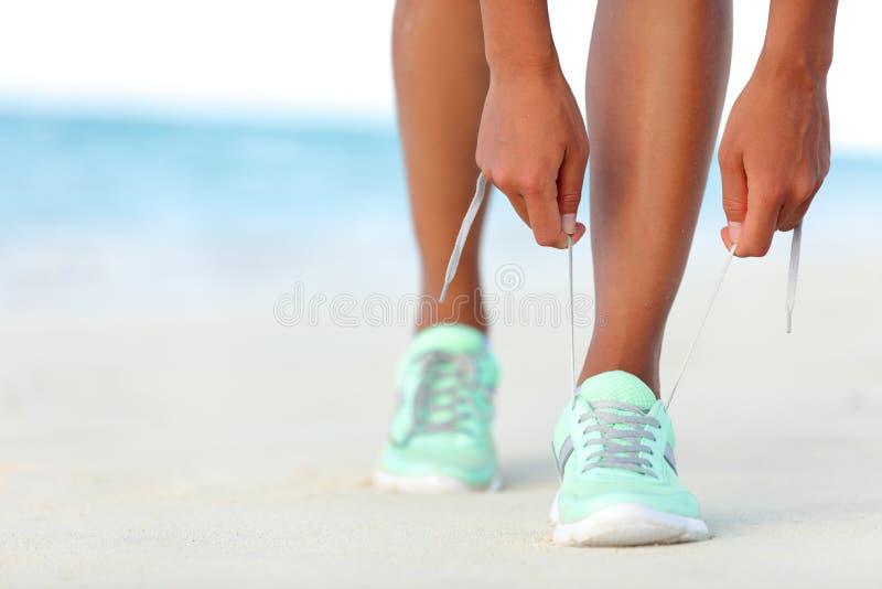 栓跑鞋的鞋带赛跑者妇女为海滩跑步做准备 图库摄影