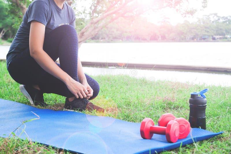 栓鞋子的体育衣物的亚裔妇女准备好锻炼在公园、锻炼和健康生活方式 免版税库存照片
