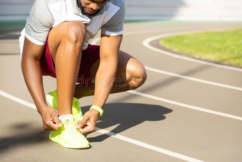 栓鞋带的严肃的有胡子的非裔美国人的运动人 免版税库存图片