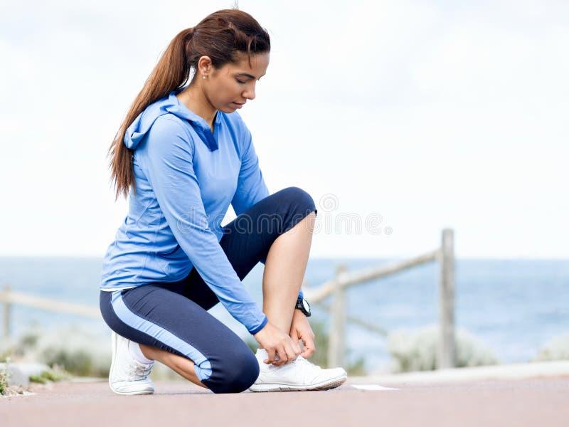 栓鞋带的妇女赛跑者在海边 库存图片