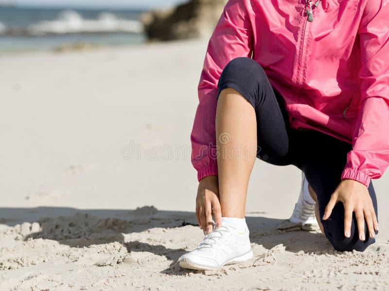 栓鞋带的妇女赛跑者在海边 库存照片