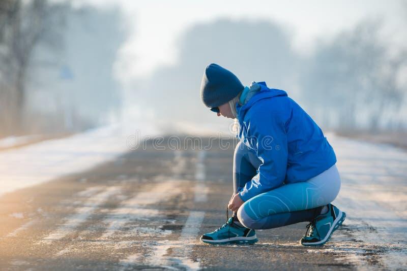 栓鞋带的妇女赛跑者 健康生活方式 免版税库存照片