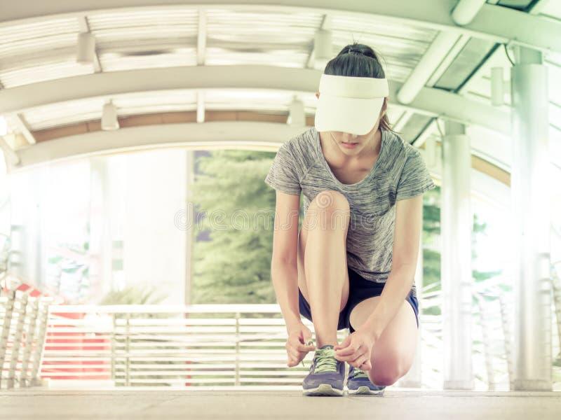 栓鞋带的少妇 为起动赛跑做准备 免版税库存图片