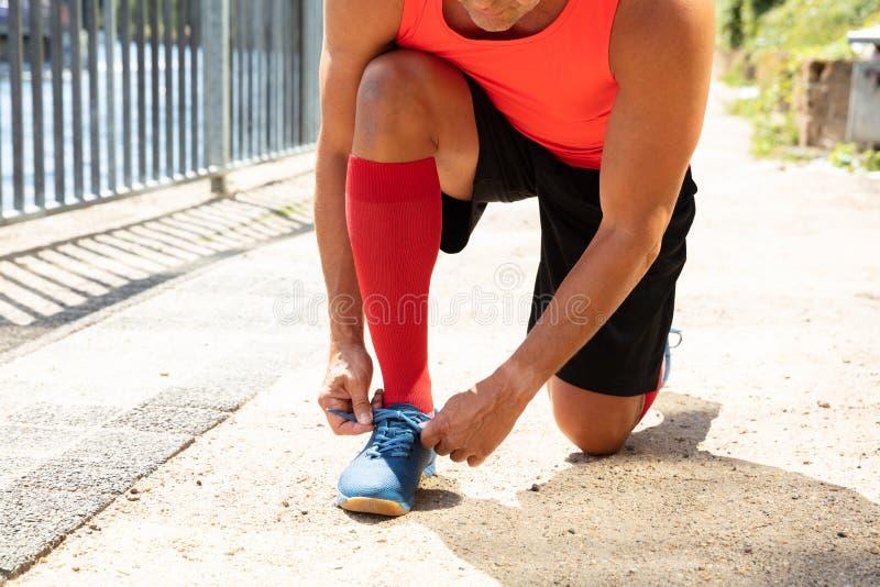 栓鞋带的男性运动员 库存照片