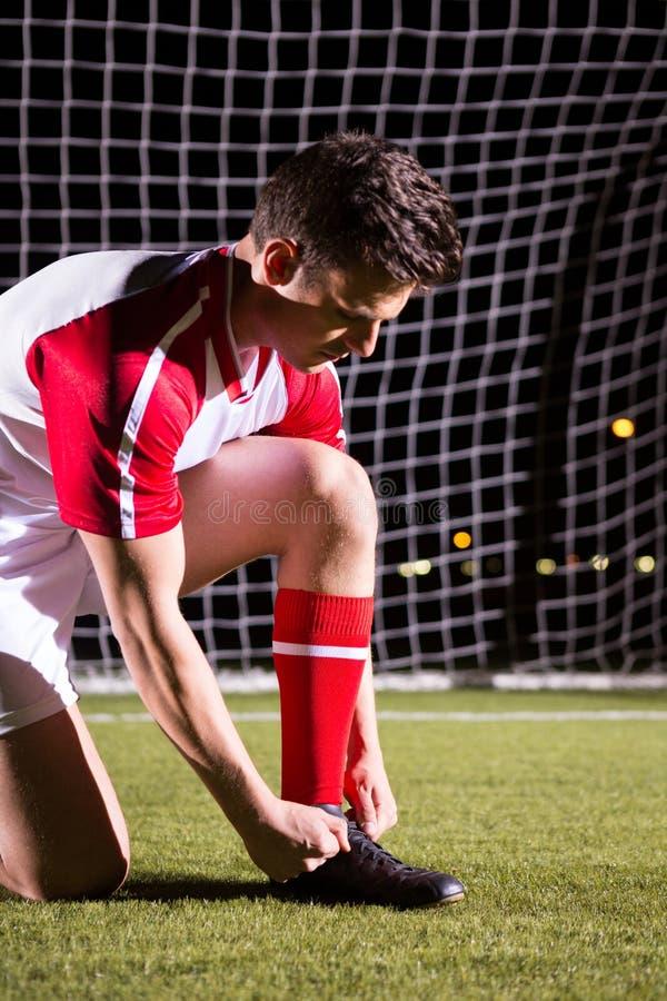 栓鞋带的年轻男性足球运动员反对目标岗位 库存照片