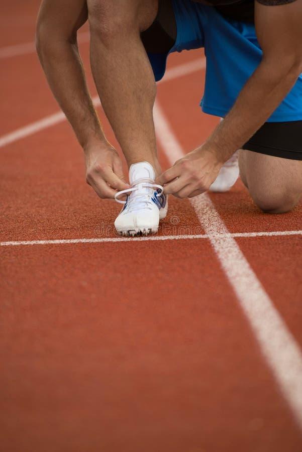 栓他的在一条连续轨道的年轻人赛跑者鞋子 鞋带,都市慢跑者 免版税库存照片
