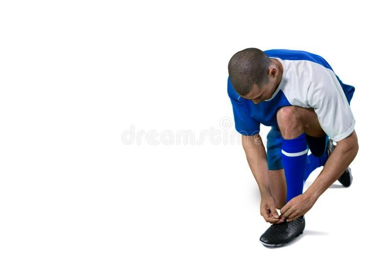 栓他的鞋带的足球运动员 免版税库存图片