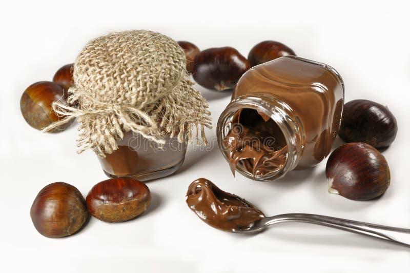 栗子和巧克力奶油在小的瓶子 免版税库存照片