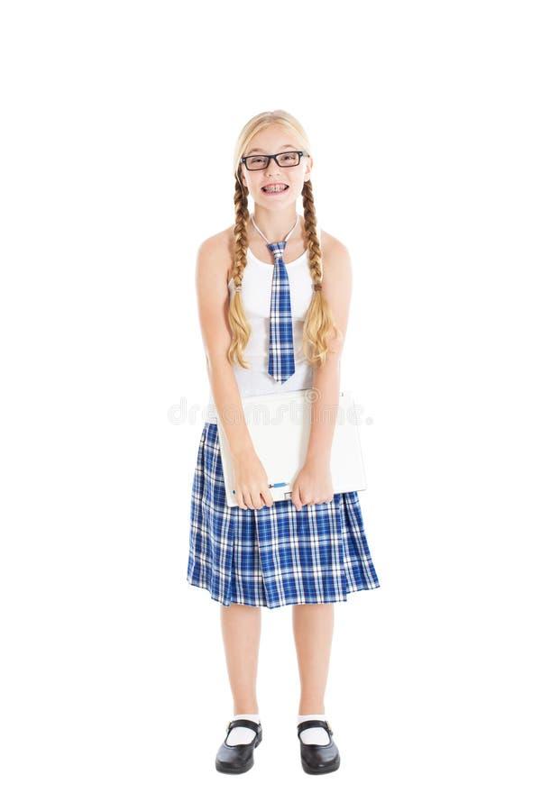 戴校服和眼镜的十几岁的女孩拿着膝上型计算机。 微笑的面孔,在您的牙的括号。 库存图片
