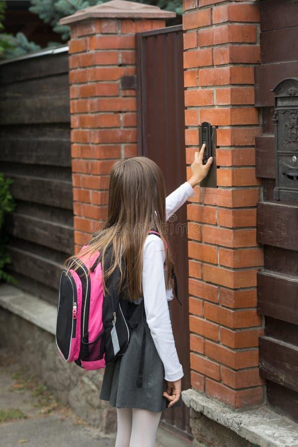 校服敲响的门铃的小女孩 免版税库存图片