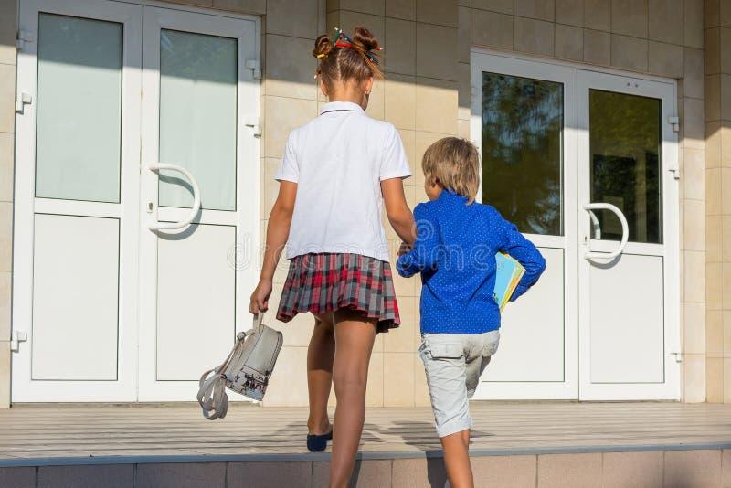 校服的一个女孩引导她的弟弟到学校 库存照片