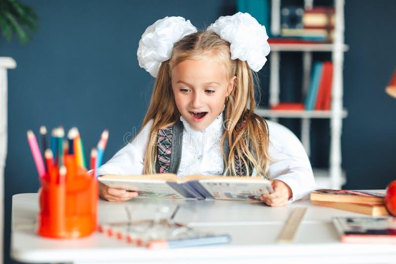 校服的一个女孩看与一张惊奇的面孔的一本课本 设法的女孩学习有许多家庭作业这是 图库摄影