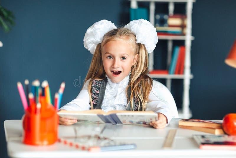 校服的一个女孩看与一张惊奇的面孔的一本课本 设法的女孩学习有许多家庭作业这是 免版税库存图片