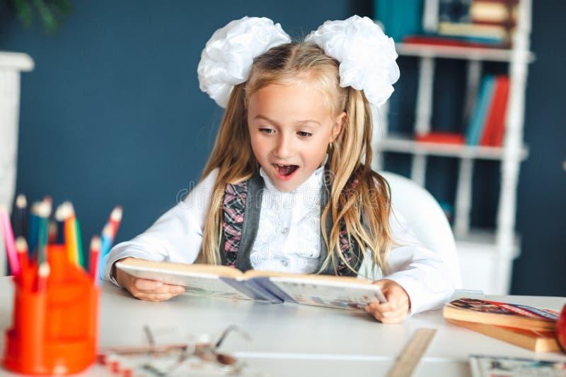 校服的一个女孩看与一张惊奇的面孔的一本课本 设法的女孩学习有许多家庭作业这是 免版税库存照片