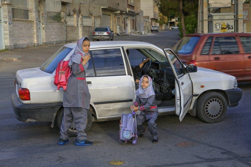 校服的两个回教女孩离开了汽车 库存图片