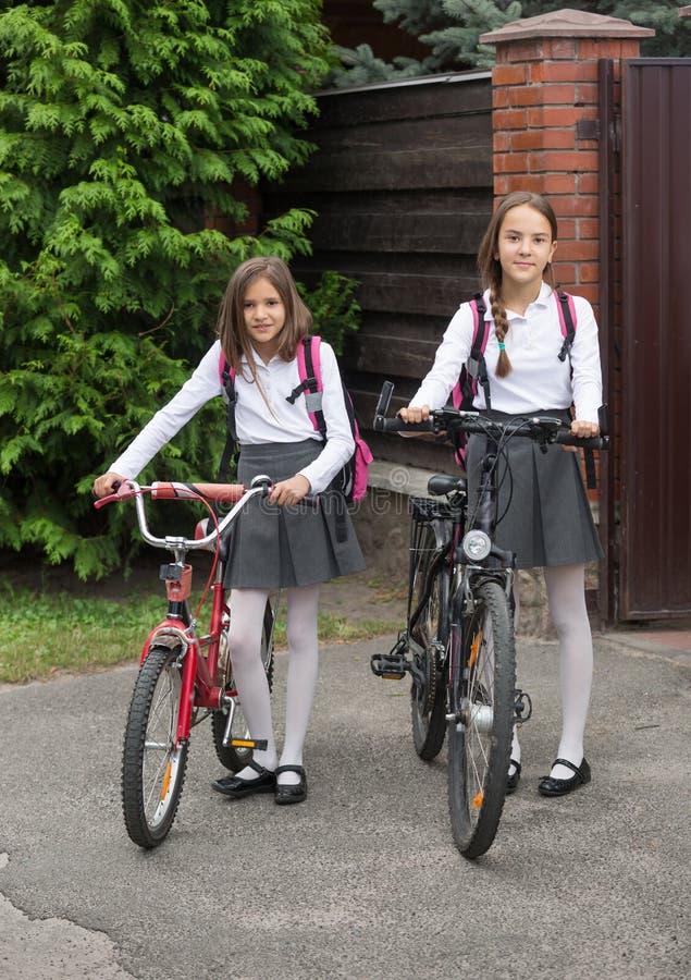 校服的两个微笑的女孩走与在str的自行车的 免版税图库摄影