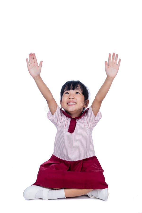 校服的亚裔矮小的中国女孩坐地板 免版税库存照片