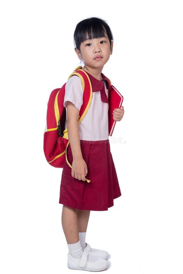 校服的亚裔矮小的中国女孩有书包的 免版税库存照片