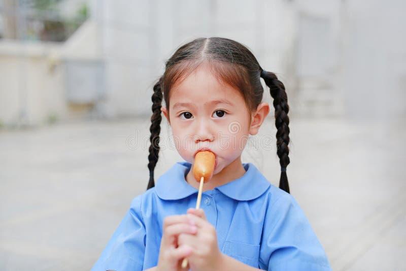校服的可爱的矮小的亚裔儿童女孩喜欢吃香肠 免版税图库摄影